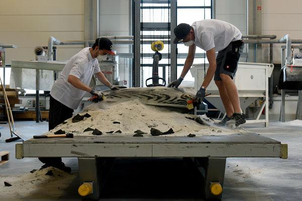 Foto: Nachbearbeitung der 3D-gedruckten Schalungs-elemente. Lose Sandpartikel werden aus dem Druckbett entfernt.