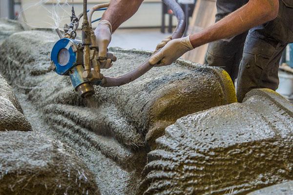 Foto: Faserverstärkter Beton wird in mehreren Schichten in die 3D-gedruckte Schalung gespritzt.